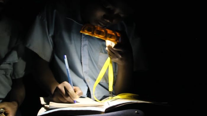 "A person in the dark who can write thanks to the sustainable little sun flashlight.<span class=""sr-only""> (opened in a new window/tab)</span>"
