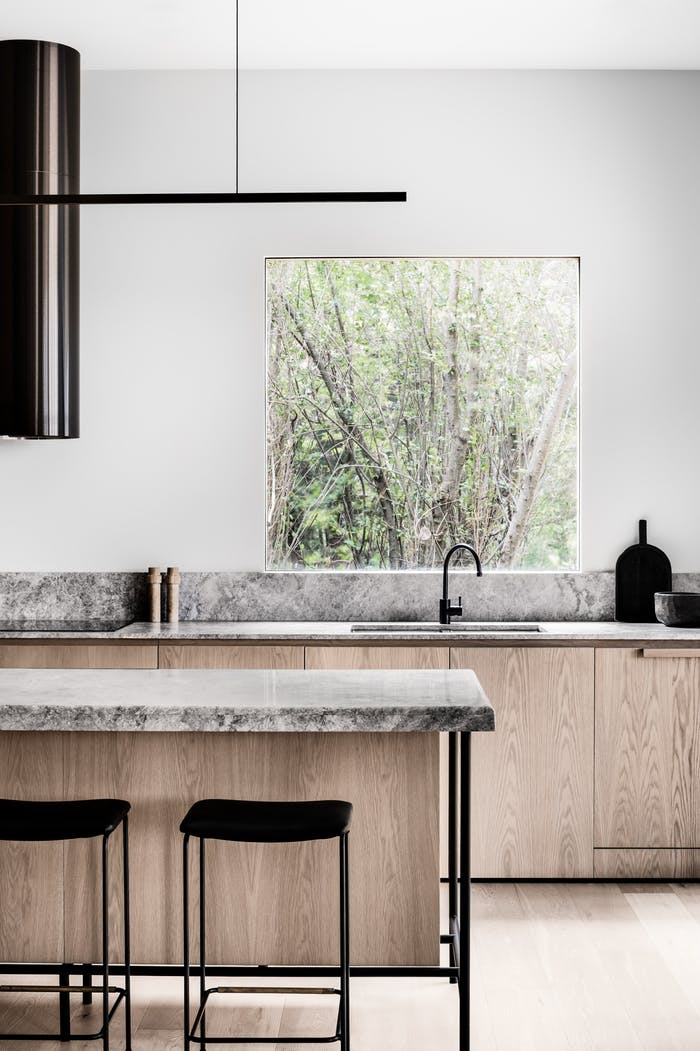 "Minimalist kitchen with wood cabinets and stone countertops, great example of biophilic design.<span class=""sr-only""> (opened in a new window/tab)</span>"