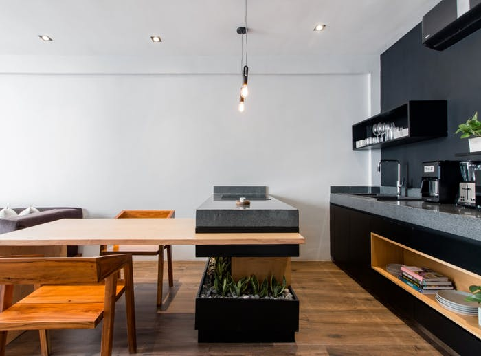 "In this minimal apartment, a built-in planter wraps around the kitchen island, creating the perfect spot for plants.<span class=""sr-only""> (opened in a new window/tab)</span>"