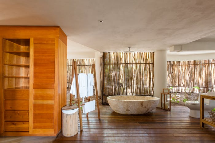 "Bathroom of Casa Nalum: the wall is made of bamboo canes that let plenty of natural light in.<span class=""sr-only""> (opened in a new window/tab)</span>"