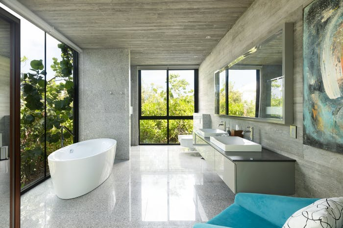 "A bathroom of Villa Islander, with a free-standing bathtub in front of the window that looks directly into nature.<span class=""sr-only""> (opened in a new window/tab)</span>"