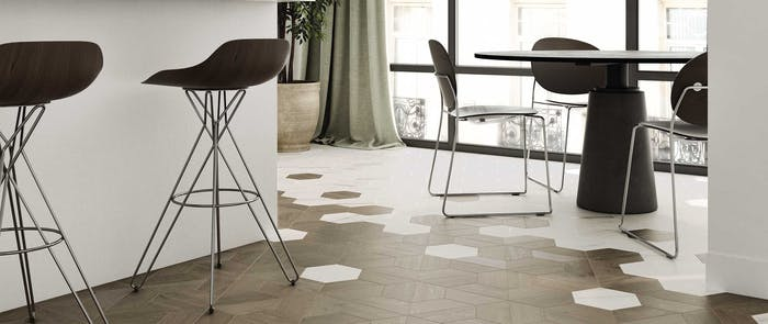 """Grey hexagonal floor tiles intersecting with a wooden flooring.<span class=""""sr-only""""> (opened in a new window/tab)</span>"""