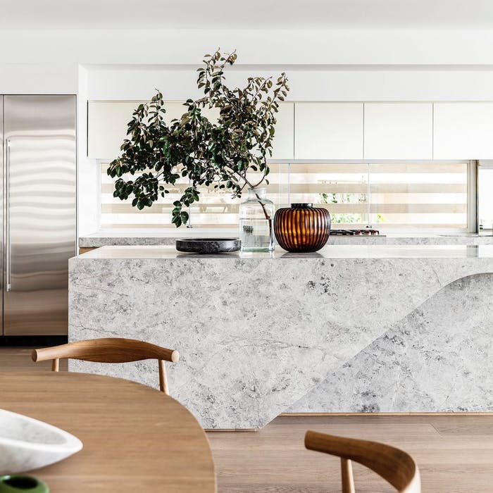 """Biophilic dining area looking into an open-plan kitchen, whose stone island and big decorative branches fill the view with natural textures.<span class=""""sr-only""""> (opened in a new window/tab)</span>"""