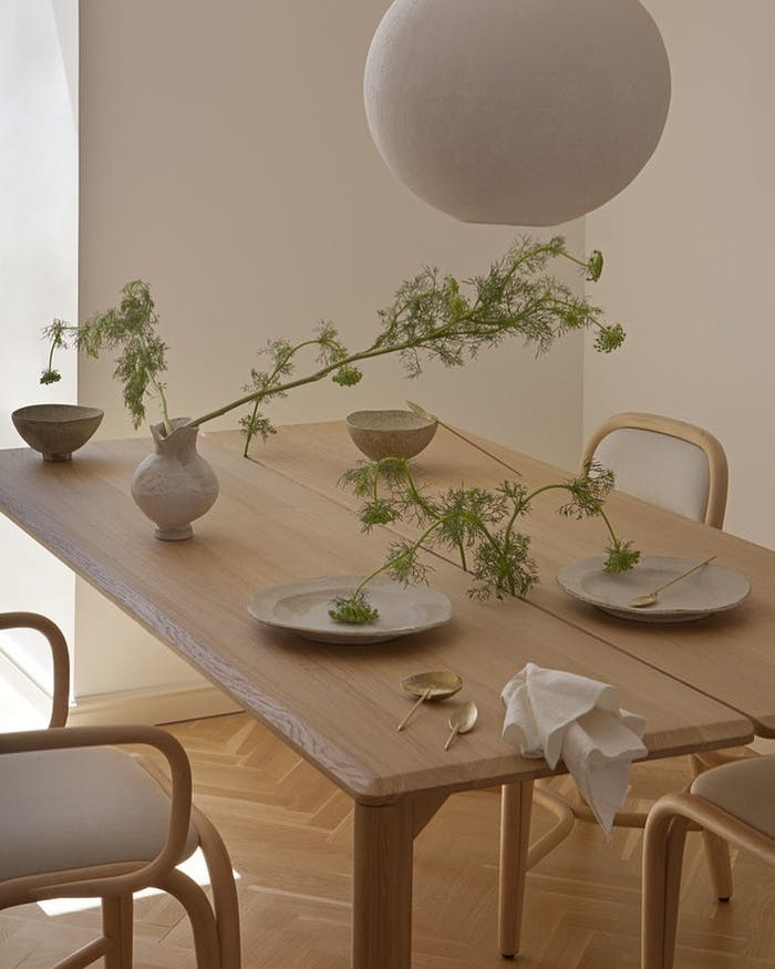 """Biophilic dining area with decorative green branches on the table.<span class=""""sr-only""""> (opened in a new window/tab)</span>"""