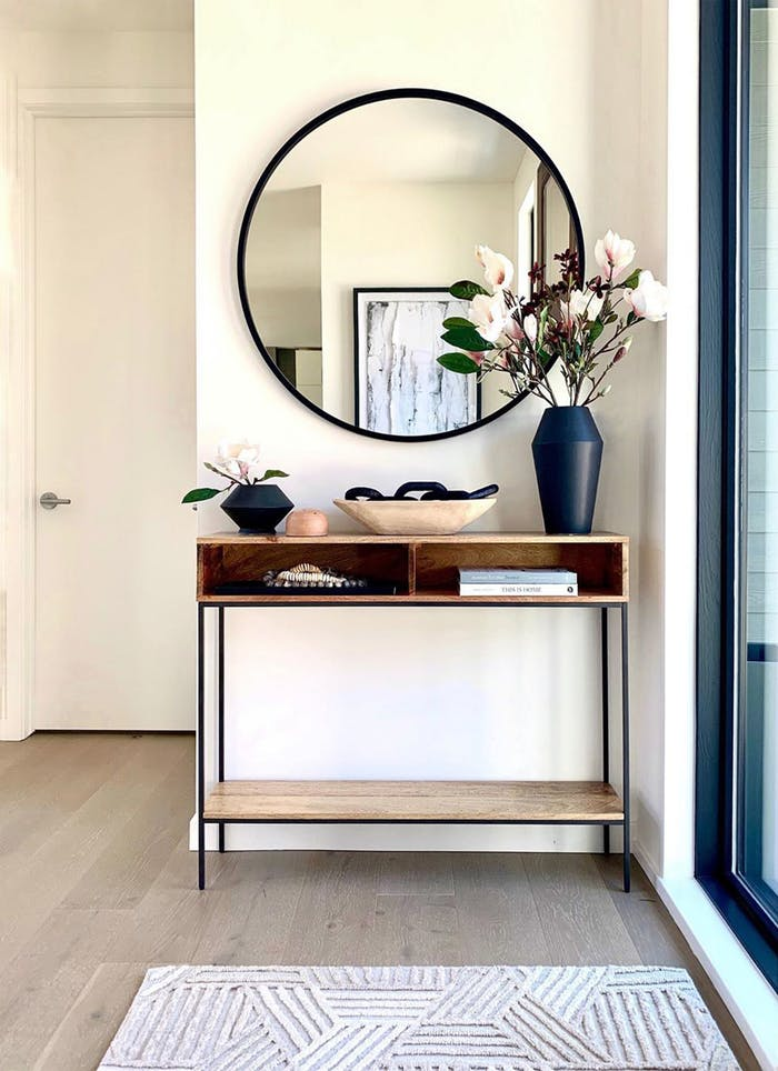 """Airy contemporary entryway with a wood console and black accents.<span class=""""sr-only""""> (opened in a new window/tab)</span>"""