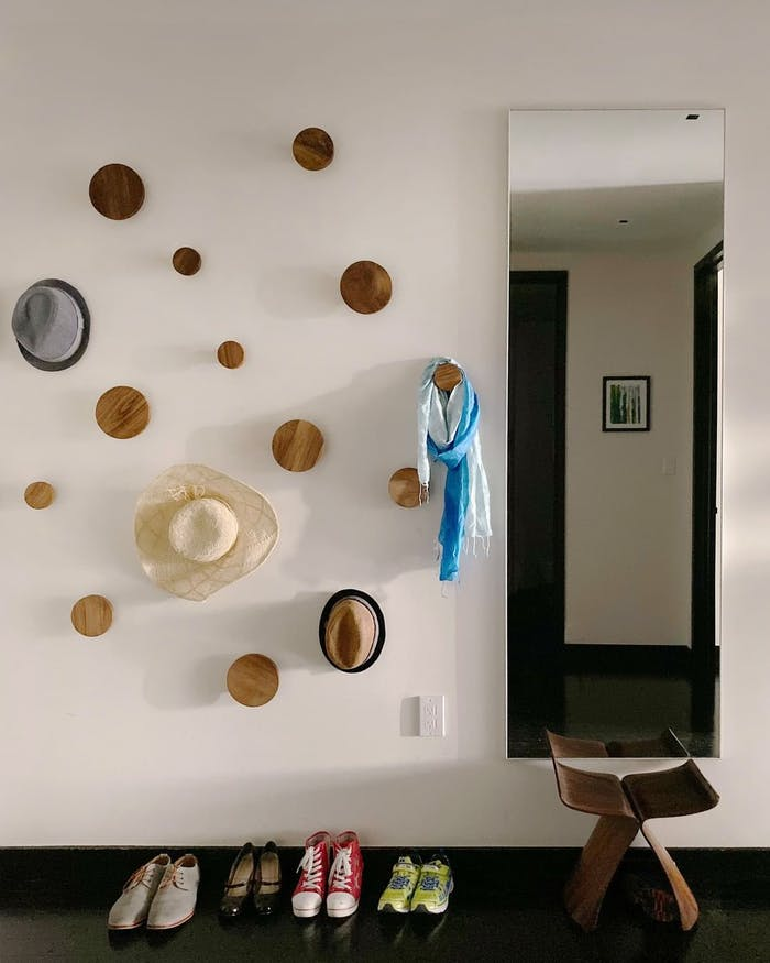 """Entryway wall with round hooks doubling as a design pattern.<span class=""""sr-only""""> (opened in a new window/tab)</span>"""