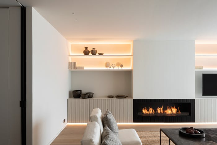 "Total white minimal living room with black fireplace as a focal point.<span class=""sr-only""> (opened in a new window/tab)</span>"