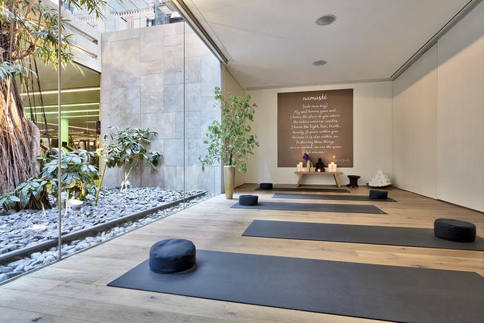 """Meditation room with a full-height window looking into a patio rich in greenery.<span class=""""sr-only""""> (opened in a new window/tab)</span>"""