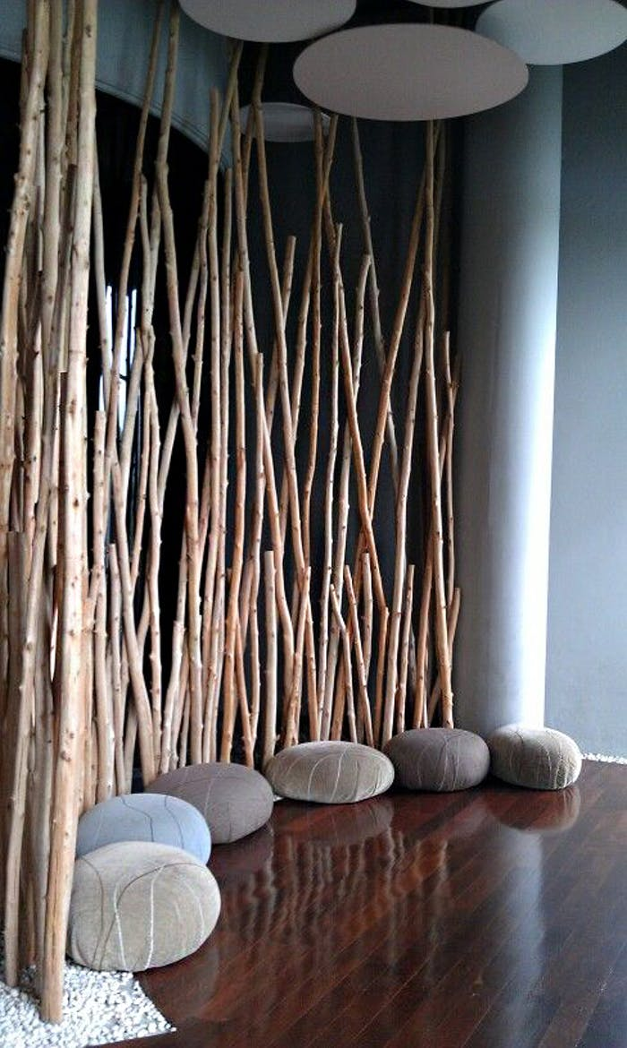 """Meditation space with felt poufs that resemble rocks and wood branches a room divider.<span class=""""sr-only""""> (opened in a new window/tab)</span>"""
