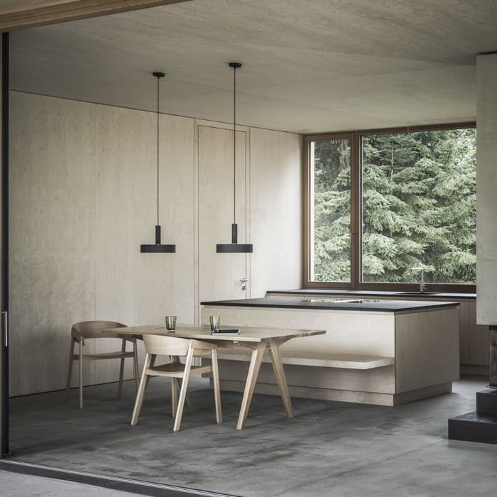 """Minimalist dining area with an open view onto greeenery.<span class=""""sr-only""""> (opened in a new window/tab)</span>"""