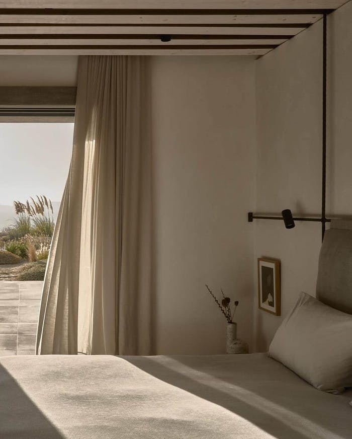 """Minimalist bedroom with curtains swinging in the wind.<span class=""""sr-only""""> (opened in a new window/tab)</span>"""