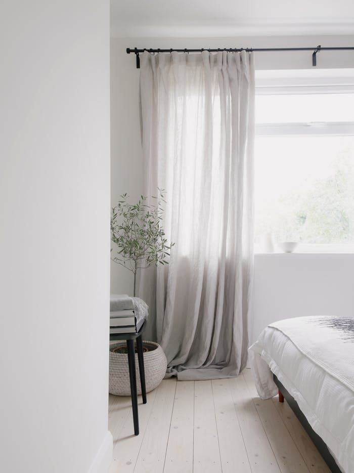 """Total-white bedroom with curtains moving in the breeze.<span class=""""sr-only""""> (opened in a new window/tab)</span>"""