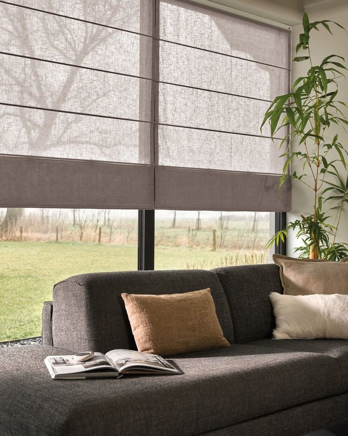 """Roman blinds creating shadow on a sofa area.<span class=""""sr-only""""> (opened in a new window/tab)</span>"""