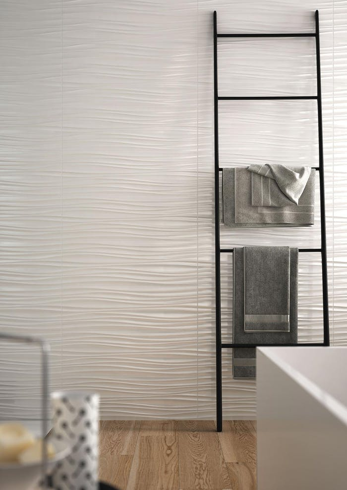 """Bathroom wall with textured tiles recalling the wavy shape of sand moved by the wind.<span class=""""sr-only""""> (opened in a new window/tab)</span>"""