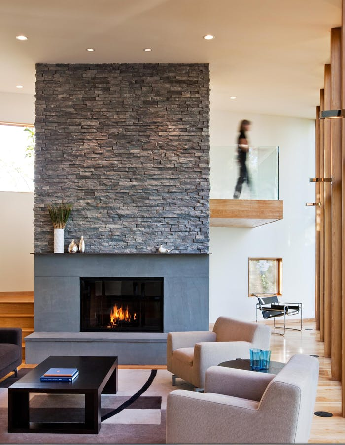 """A contemporary living room with huge fireplace cladded in dark stone.<span class=""""sr-only""""> (opened in a new window/tab)</span>"""