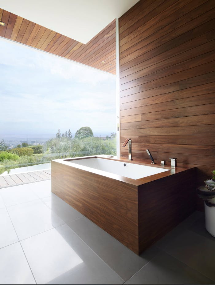 """A contemporary bathroom with smooth wood panels on the wall as well as around the bathtub.<span class=""""sr-only""""> (opened in a new window/tab)</span>"""