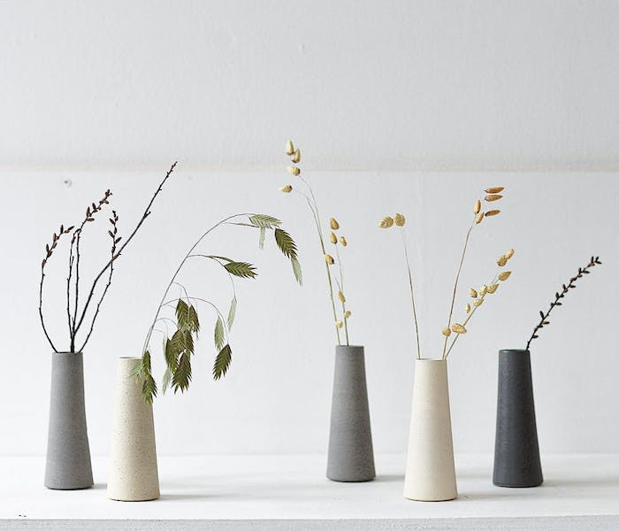 """Minimal stone vases with various stems inside.<span class=""""sr-only""""> (opened in a new window/tab)</span>"""