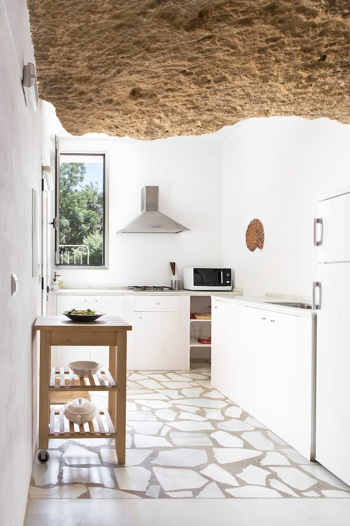 """Kitchen with rocky ceiling contrasting with the white walls and floors.<span class=""""sr-only""""> (opened in a new window/tab)</span>"""