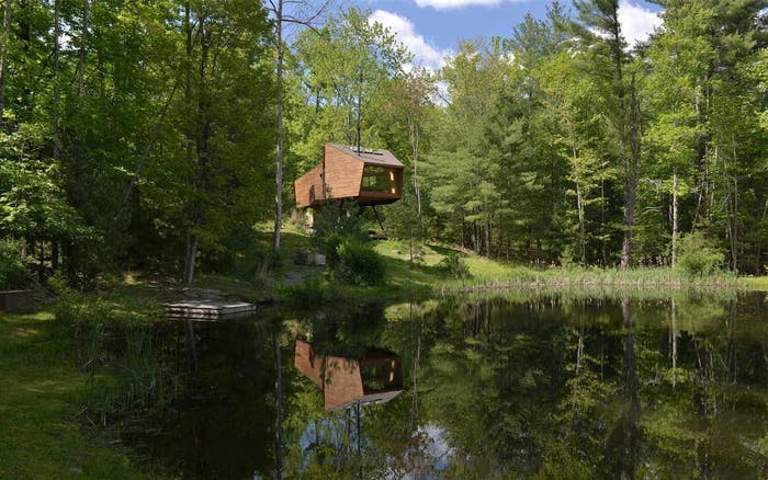 """Treehouse in front of a body of water.<span class=""""sr-only""""> (opened in a new window/tab)</span>"""