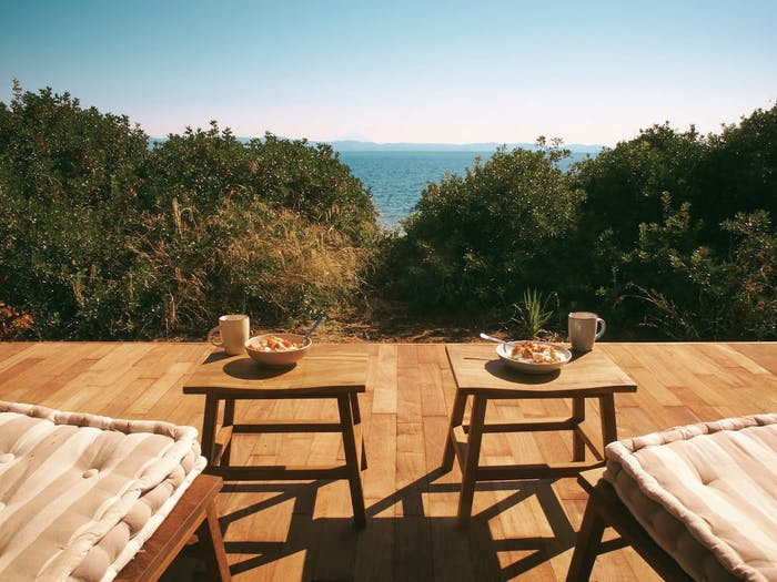 """Outdoor terrace surrounded by with trees and looking towards the ocean.<span class=""""sr-only""""> (opened in a new window/tab)</span>"""