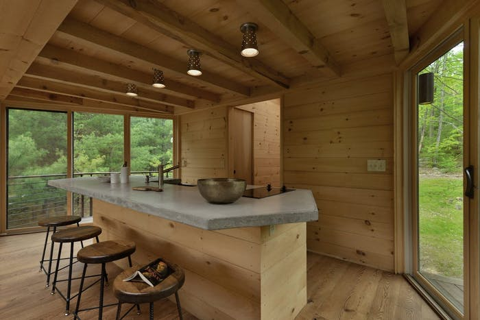"""Simple wooden kitchen framed by wooden windows looking outdoors.<span class=""""sr-only""""> (opened in a new window/tab)</span>"""