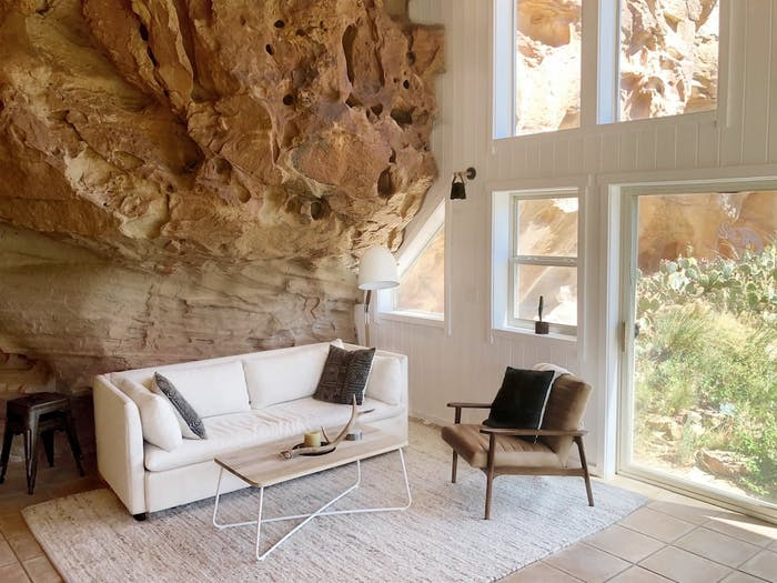 """Living room with back wall incorporating the natural rocky wall.<span class=""""sr-only""""> (opened in a new window/tab)</span>"""