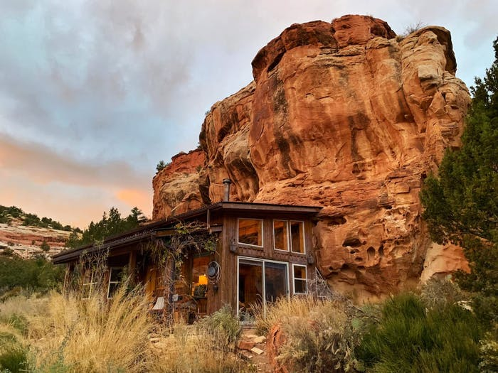 """Outside view of a house built next to a rocky wall.<span class=""""sr-only""""> (opened in a new window/tab)</span>"""