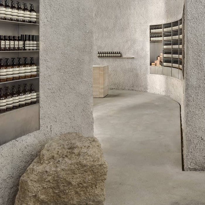 """Interior of a store with rough stone surfaces recalling local ecology.<span class=""""sr-only""""> (opened in a new window/tab)</span>"""