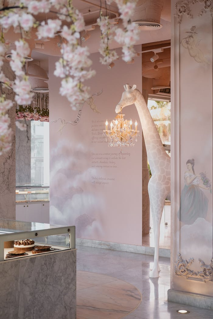 """Store interior with flowers hanging from the ceiling and a tall giraffe floor lamp.<span class=""""sr-only""""> (opened in a new window/tab)</span>"""
