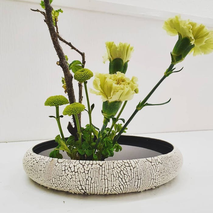 """Minimal arrangement with green and yellow flowers.<span class=""""sr-only""""> (opened in a new window/tab)</span>"""