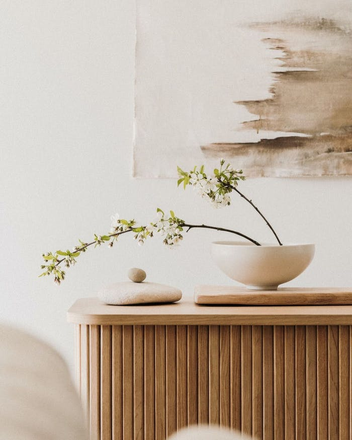 """Simple arrangement with leafy branches and tiny white flowers in a white bowl.<span class=""""sr-only""""> (opened in a new window/tab)</span>"""