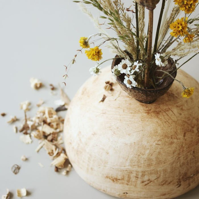 """Close-up of small yellow flowers and pampas grass in a vase.<span class=""""sr-only""""> (opened in a new window/tab)</span>"""