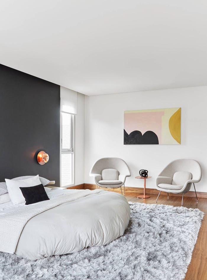 """Minimal bedroom in the tones of beige with a pink geometric artwork.<span class=""""sr-only""""> (opened in a new window/tab)</span>"""