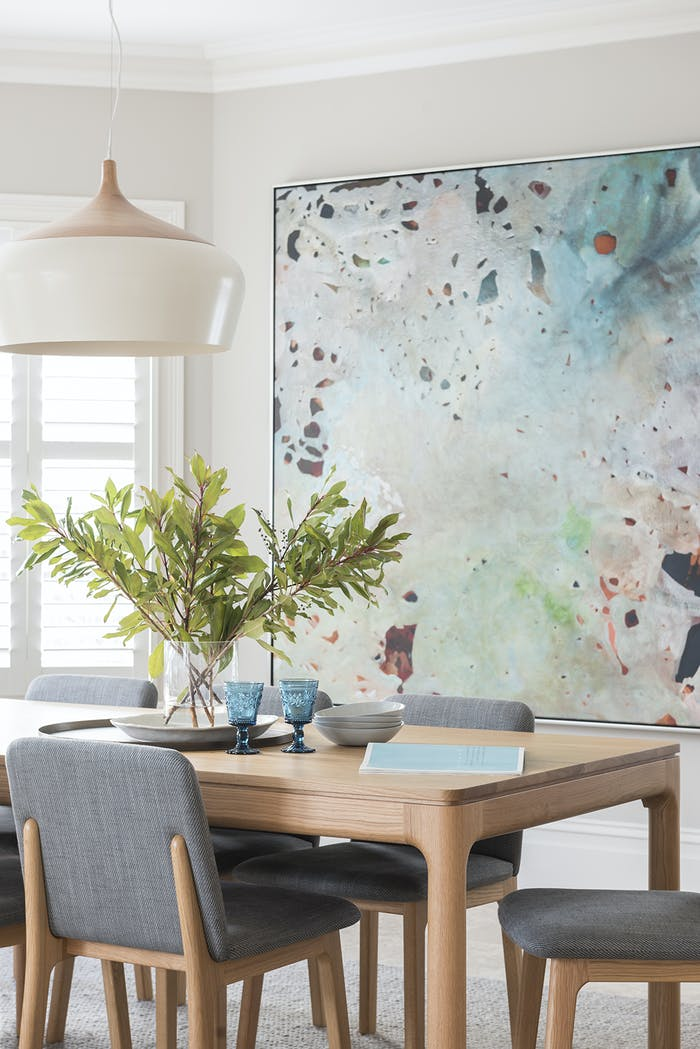 """Minimal dining room with a colourful artwork and matching glasses on the table.<span class=""""sr-only""""> (opened in a new window/tab)</span>"""