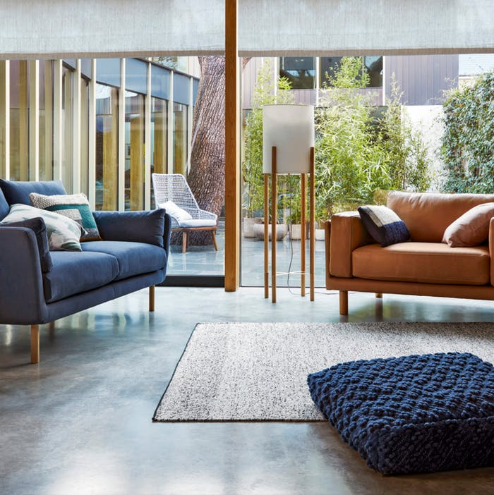 """Living room with plenty of cushions, a rug and a floor cushion to add coziness.<span class=""""sr-only""""> (opened in a new window/tab)</span>"""