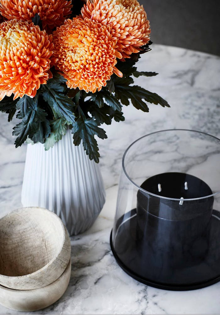 """Close-up of a styling with a black candle, wooden bowl and bold orange flowers.<span class=""""sr-only""""> (opened in a new window/tab)</span>"""