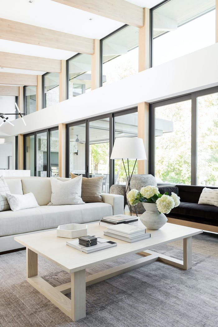 """Minimal living room with a vase full of white hydrangea flowers.<span class=""""sr-only""""> (opened in a new window/tab)</span>"""