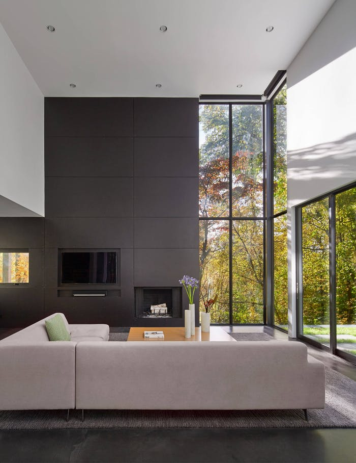 """Minimal living room with full-height windows looking into nature. The sofa is placed on the windows.<span class=""""sr-only""""> (opened in a new window/tab)</span>"""