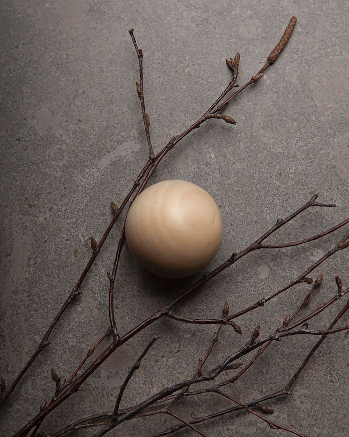 """Branches arranged onto a grey surface with a light wood sphere next to them.<span class=""""sr-only""""> (opened in a new window/tab)</span>"""