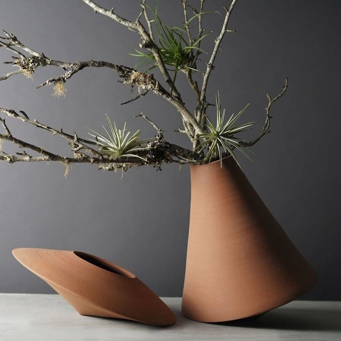 """Branches with touches of green arranged in a slanted vase.<span class=""""sr-only""""> (opened in a new window/tab)</span>"""