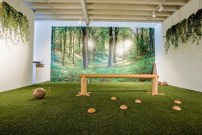 "Another view of a biophilic gym. The overall feel is to be immersed in nature, and is achieved with real plants and nature-inspired finishes like a mural depicting a forest and a grass-like carpet.<span class=""sr-only""> (opened in a new window/tab)</span>"