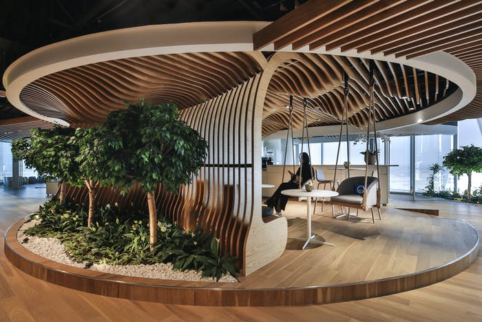 "Biophilic office with curved wood ceiling recalling the shape of a tree and swings hanging from the ceiling.<span class=""sr-only""> (opened in a new window/tab)</span>"