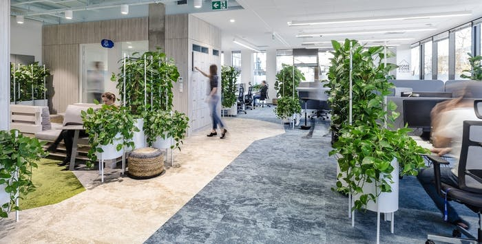 "View of a biophilic office where planters of different heights introduce greenery while partitioning the space.<span class=""sr-only""> (opened in a new window/tab)</span>"