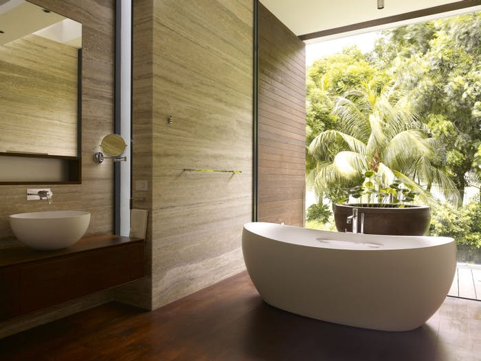 """Natural bathroom design with a floor-to-ceiling window looking into the forest.<span class=""""sr-only""""> (opened in a new window/tab)</span>"""