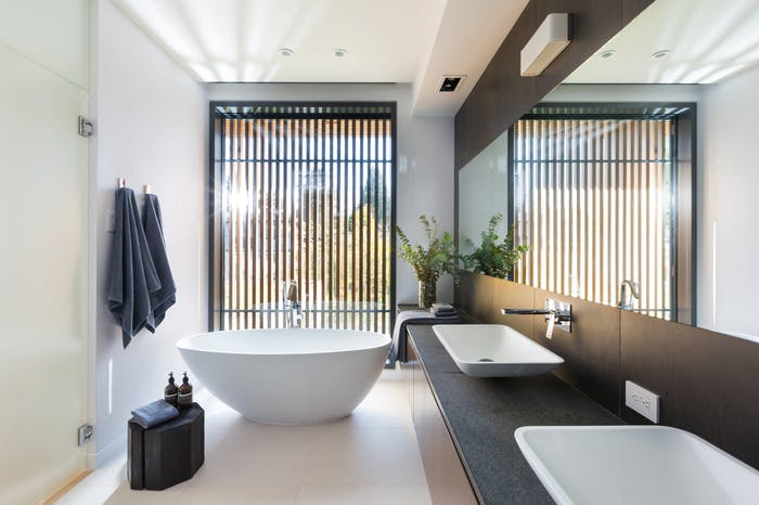 """Natural bathroom design filled with natural light. A vertical wall panelling adds privacy<span class=""""sr-only""""> (opened in a new window/tab)</span>"""