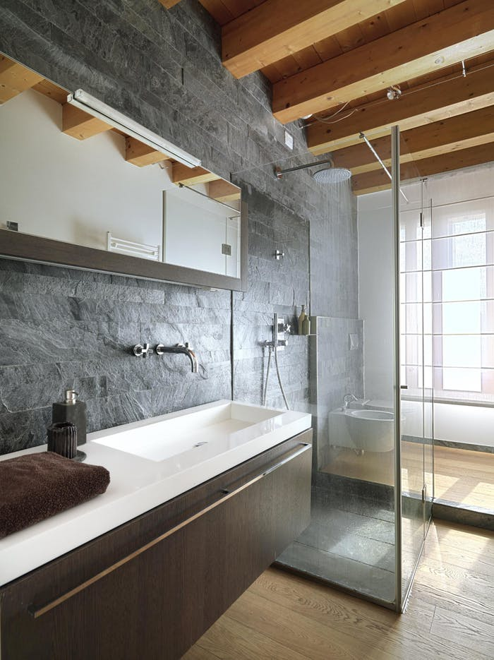 """Bathroom with stone and wood finishes.<span class=""""sr-only""""> (opened in a new window/tab)</span>"""
