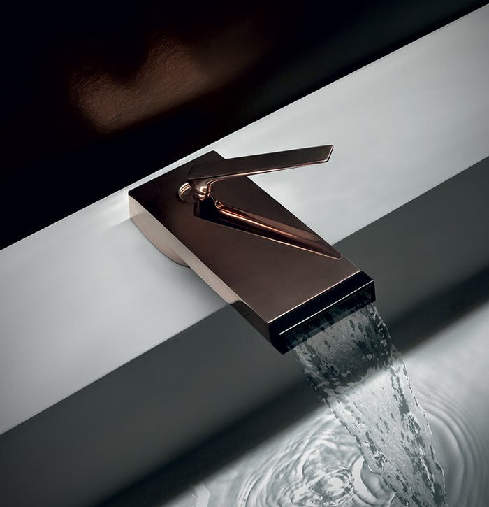 """A waterfall faucet on a modern bathtub, adding a biophilic twist to a natural bathroom design.<span class=""""sr-only""""> (opened in a new window/tab)</span>"""