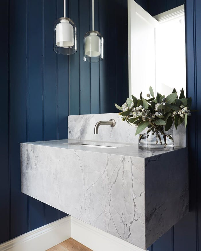"""Bathroom with blue wall, grey stone lavabo and greenery.<span class=""""sr-only""""> (opened in a new window/tab)</span>"""