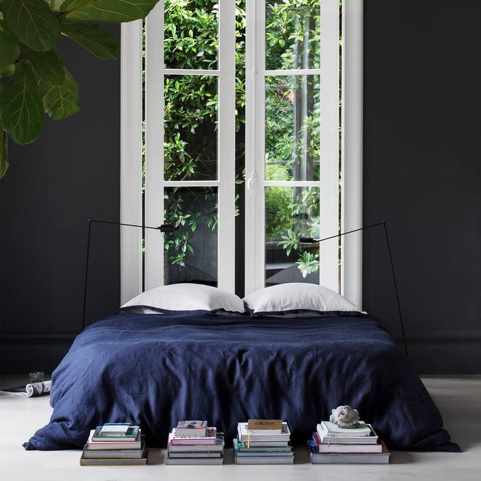 """Bedroom with bed placed against a tall window.<span class=""""sr-only""""> (opened in a new window/tab)</span>"""