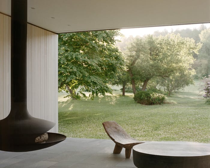"""Outdoor seating area overlooking a lush garden.<span class=""""sr-only""""> (opened in a new window/tab)</span>"""